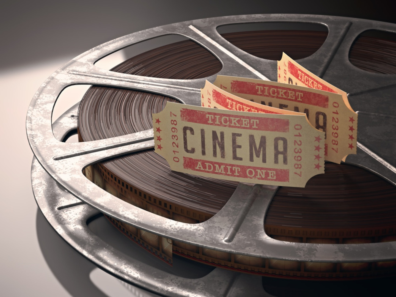 Cinema ticket over rolls of film. Concept of festival of cinema.